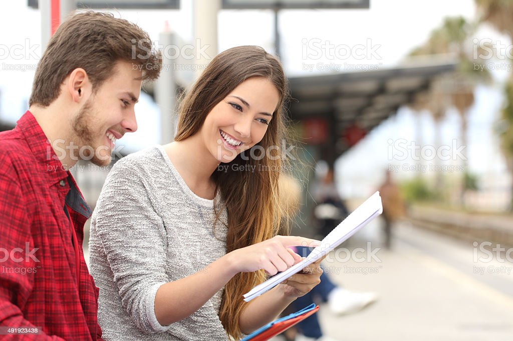 Couple of students studying in a train station stock photo