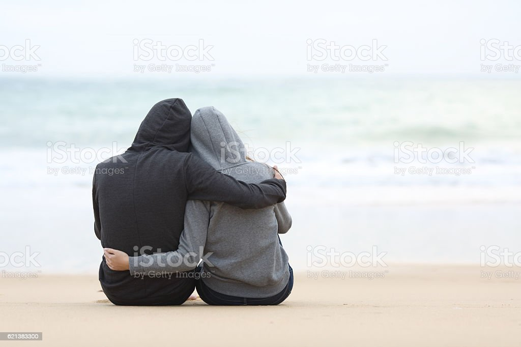 Couple of teenagers hugging watching sea stock photo