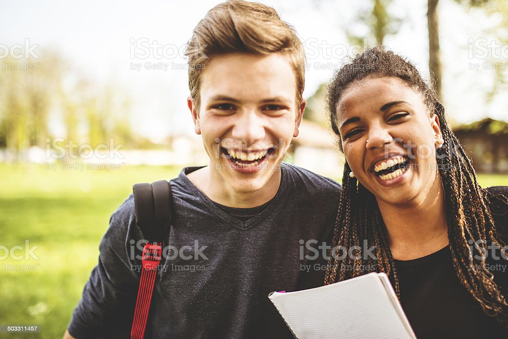 couple of teenagers student outdoors laughing stock photo