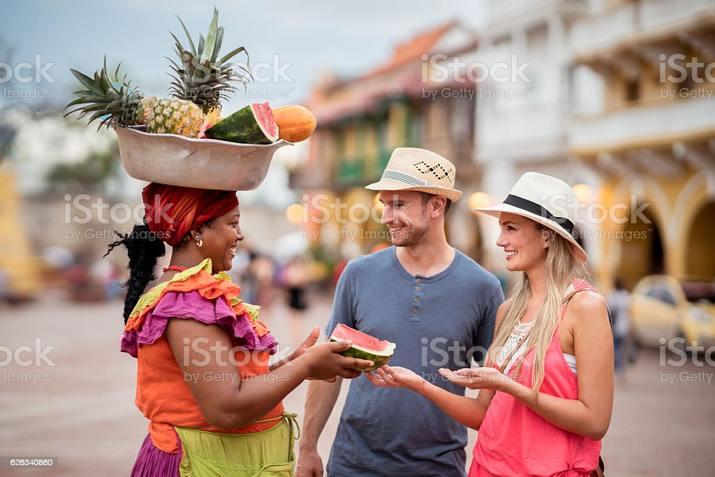 Couple of tourist buying fruits in the street stock photo