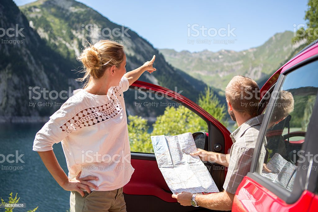 Couple of tourist with rental car reading map-Road trip stock photo