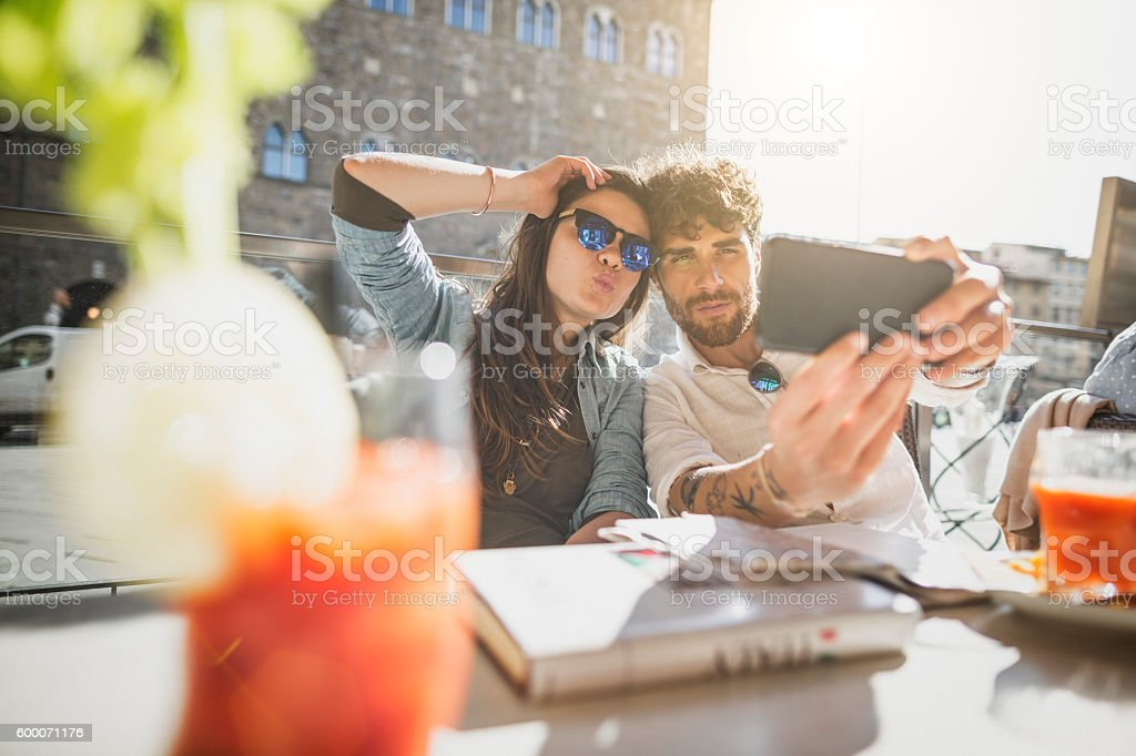 Couple of tourists at bar takes a selfie, in Firenze stock photo