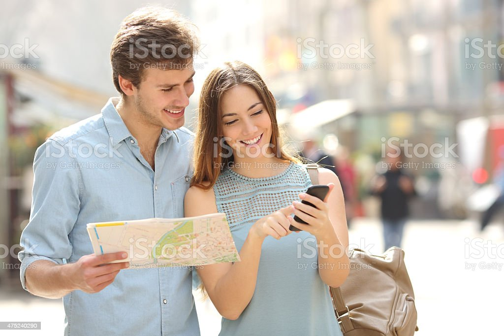 Couple of tourists consulting a city guide and smartphone gps stock photo