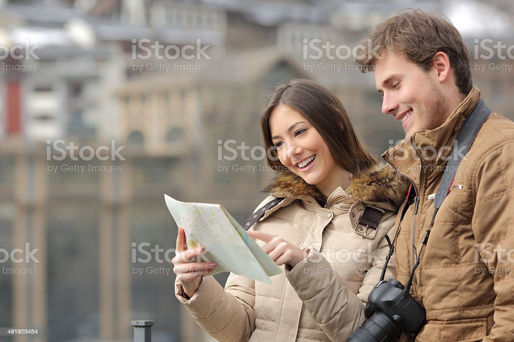 Couple of tourists consulting a guide in winter stock photo