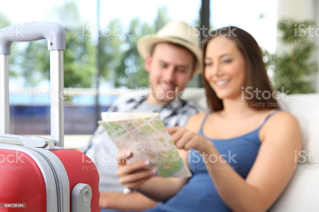 Couple of tourists searching location in a map stock photo
