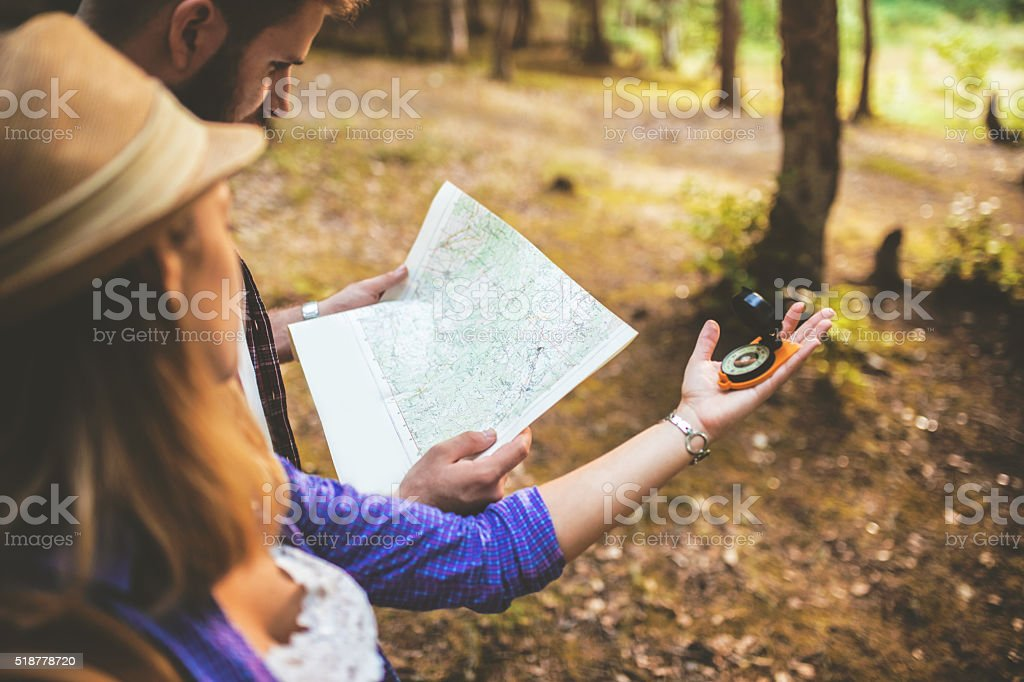 Couple of tourists using compass and map stock photo