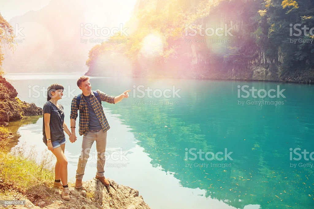couple of travelers at the gorgeous lake stock photo
