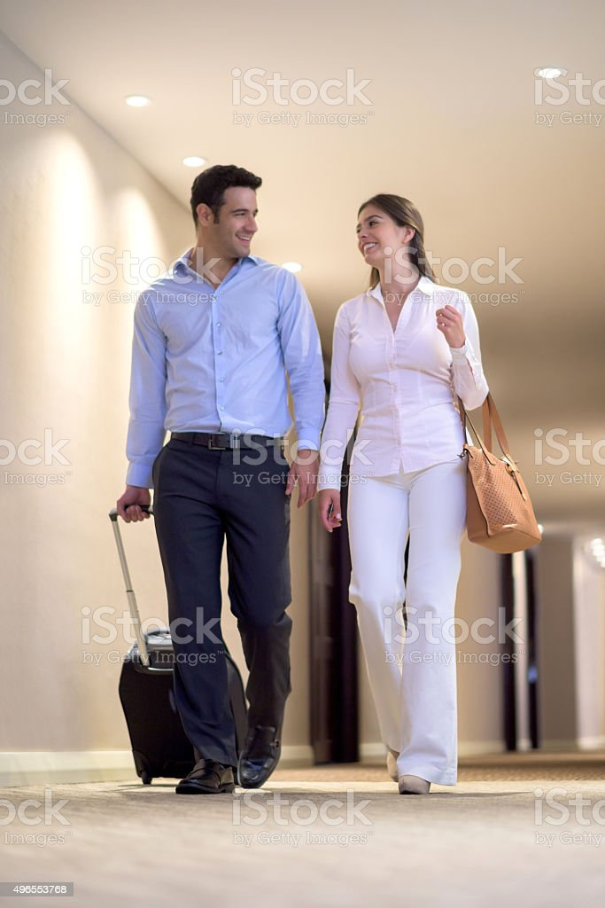 Couple of travelers walking through a hotel stock photo