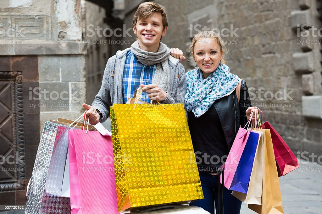 Couple of travellers with shopping bags stock photo