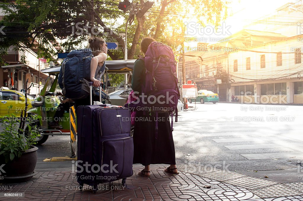 couple of woman with a travel bag standing on street stock photo