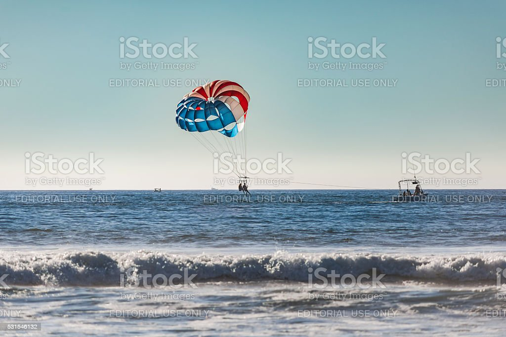 Couple of women parasailing  with blue and red parachute stock photo