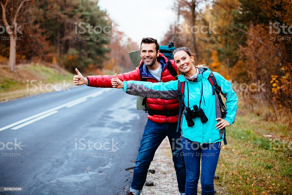 Couple of young backpackers hitchhiking stock photo