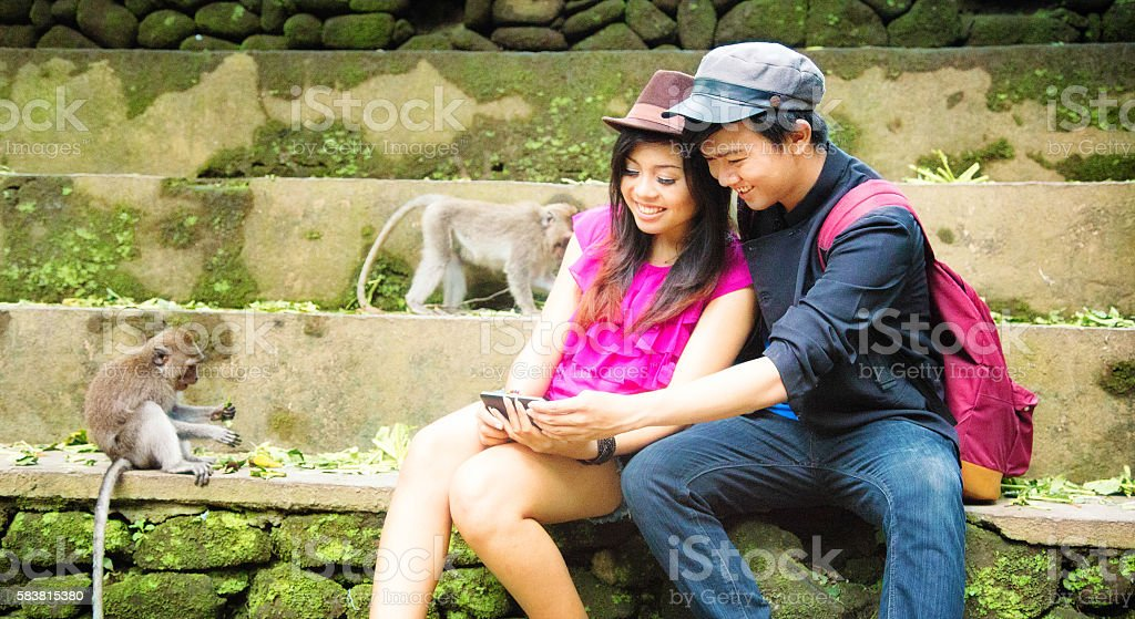 Couple of young Indonesian enjoying a game on mobile phone stock photo