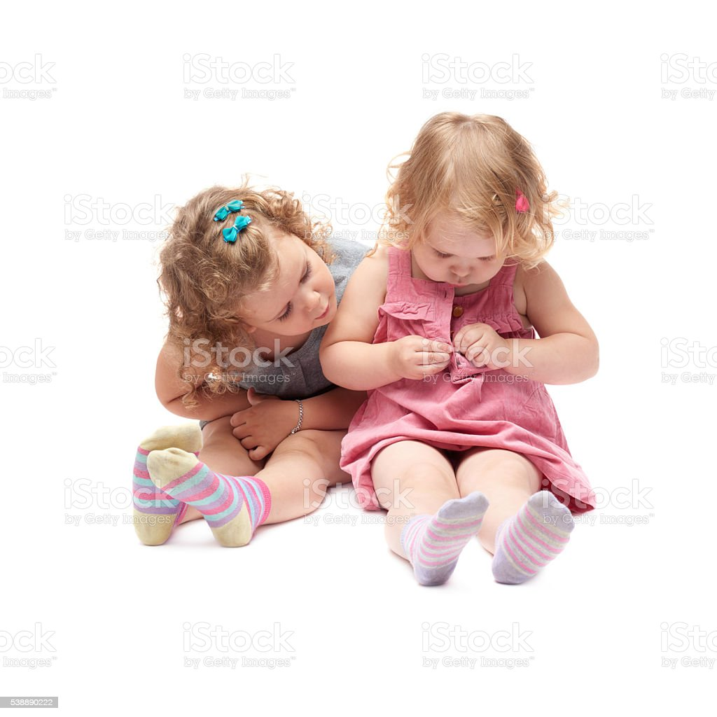 Couple of young little girl sitting over isolated white background stock photo