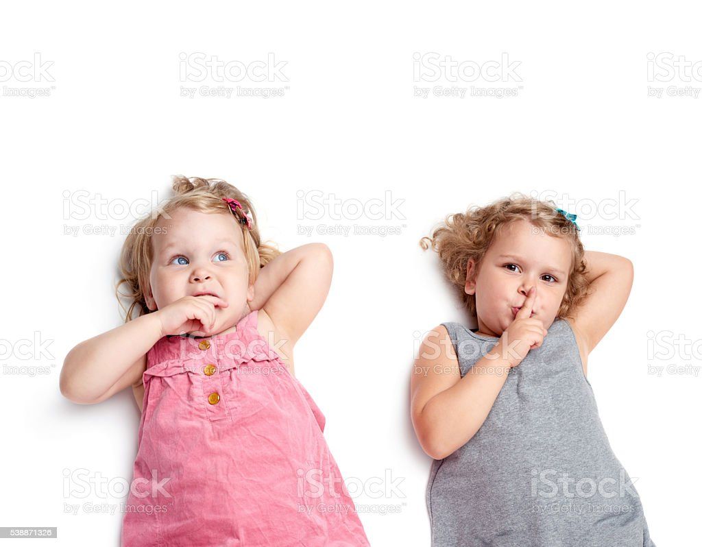Couple of young little girls lying over isolated white background stock photo