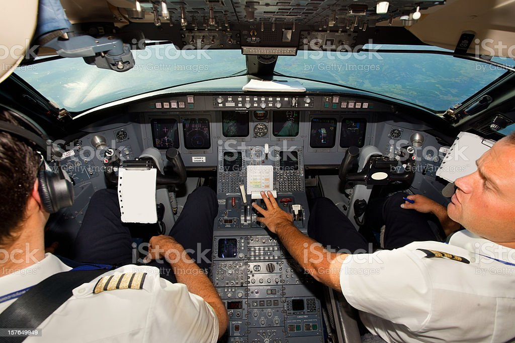 Couple of young pilots in cockpit royalty-free stock photo