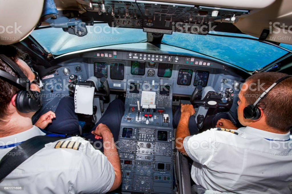 Couple of young pilots in cockpit,approaching the airport stock photo