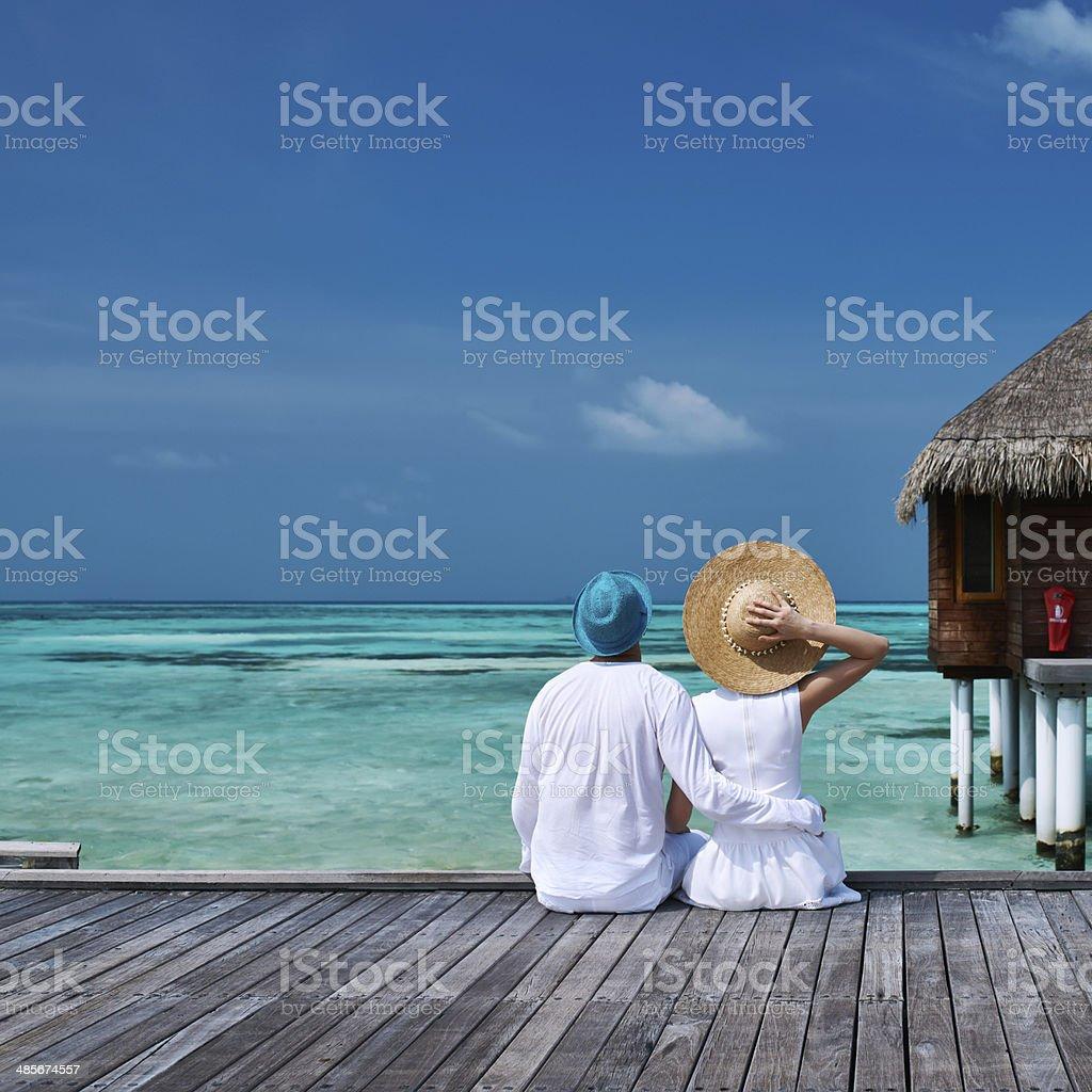 Couple on a beach jetty at Maldives stock photo