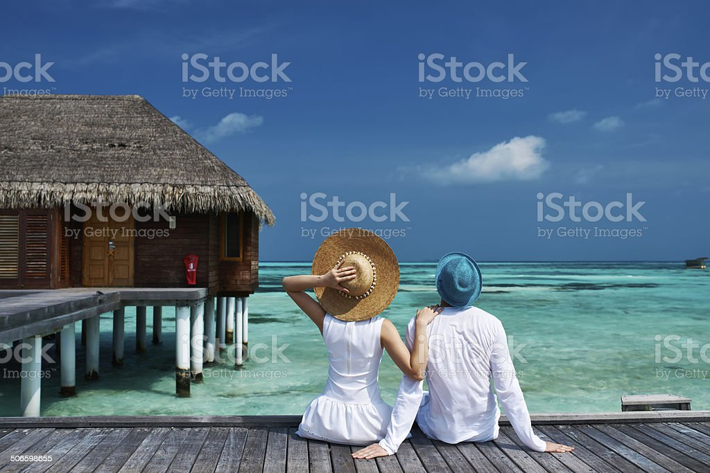 Couple on a beach jetty at Maldives stock photo