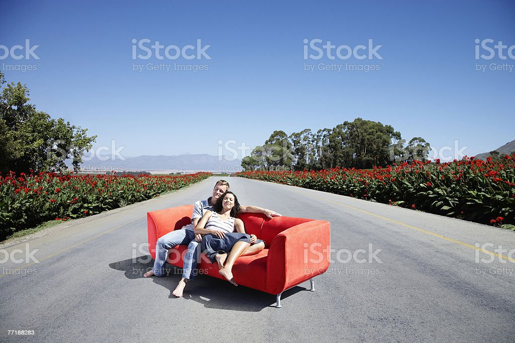A couple on a couch in the road stock photo