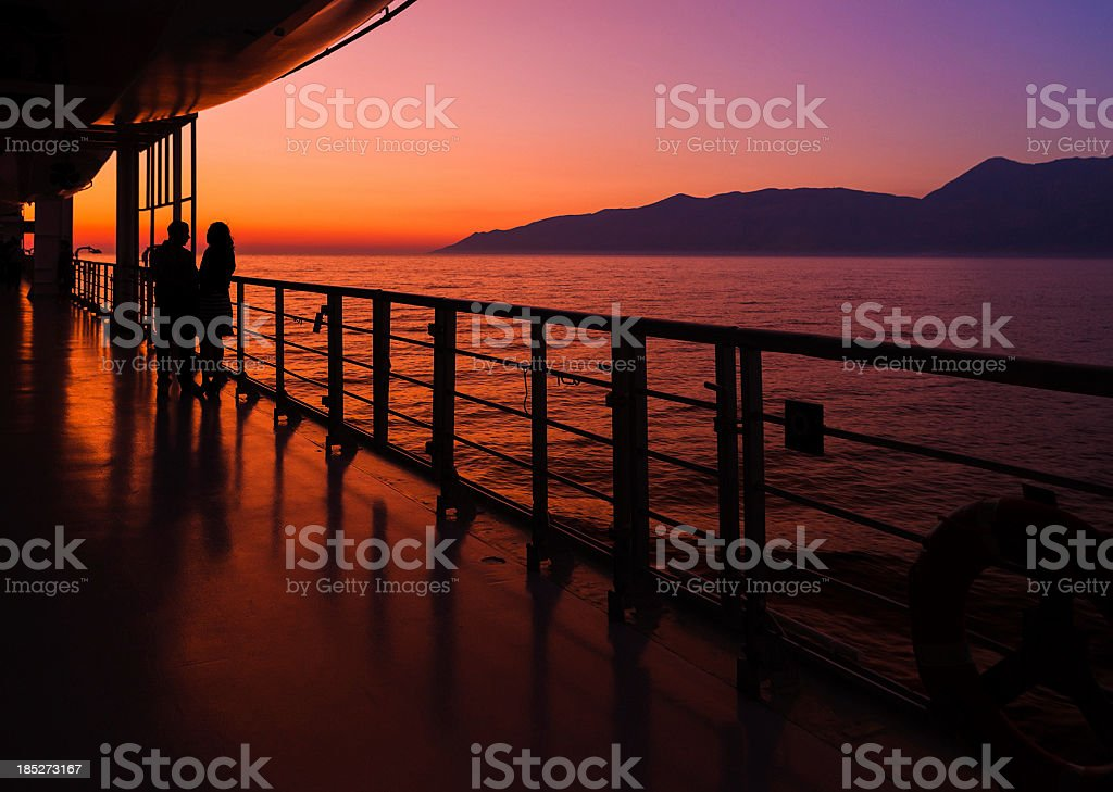 couple on a cruise ship at sunset stock photo
