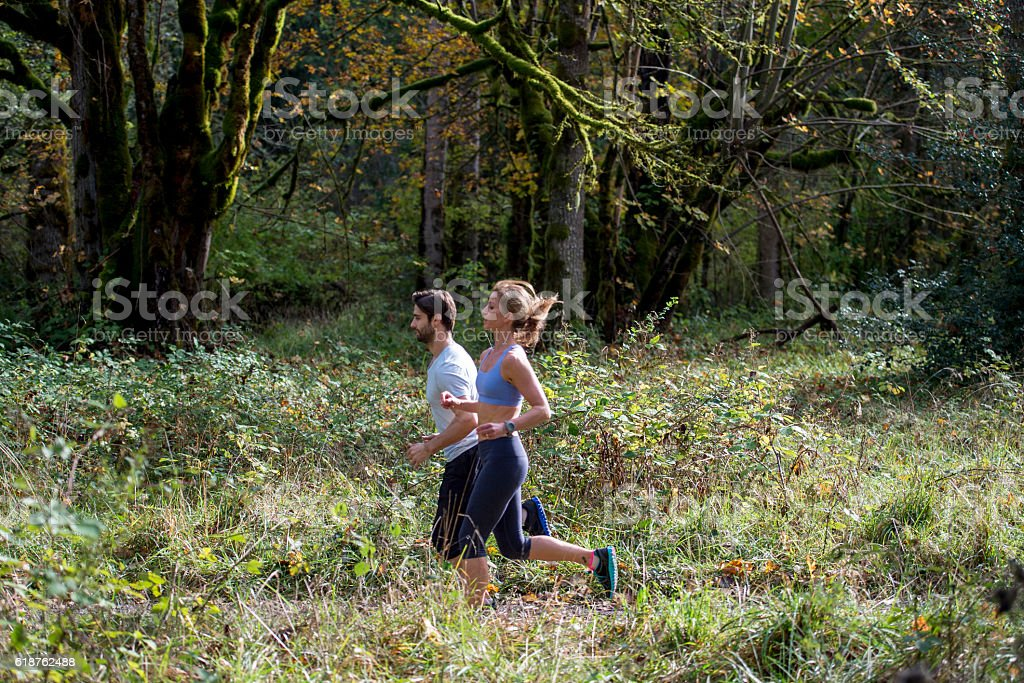 Couple on a Jog Through the Forest stock photo