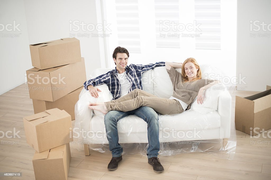 Couple on a white love seat surrounded by moving boxes stock photo