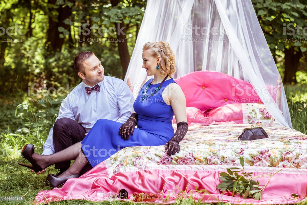 A couple on bed in meadow stock photo