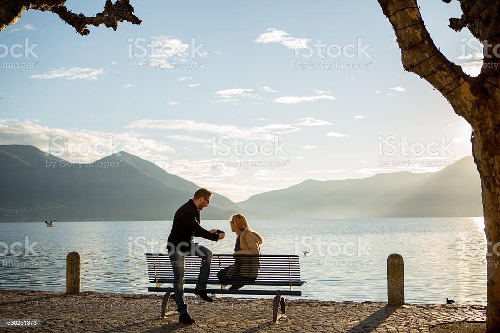 Paar auf Bank in der Nähe von See, die am Telefon-Herbst in Europa – Foto