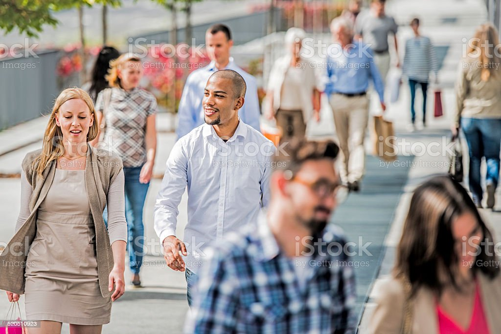 Couple on crowded city street after shopping stock photo