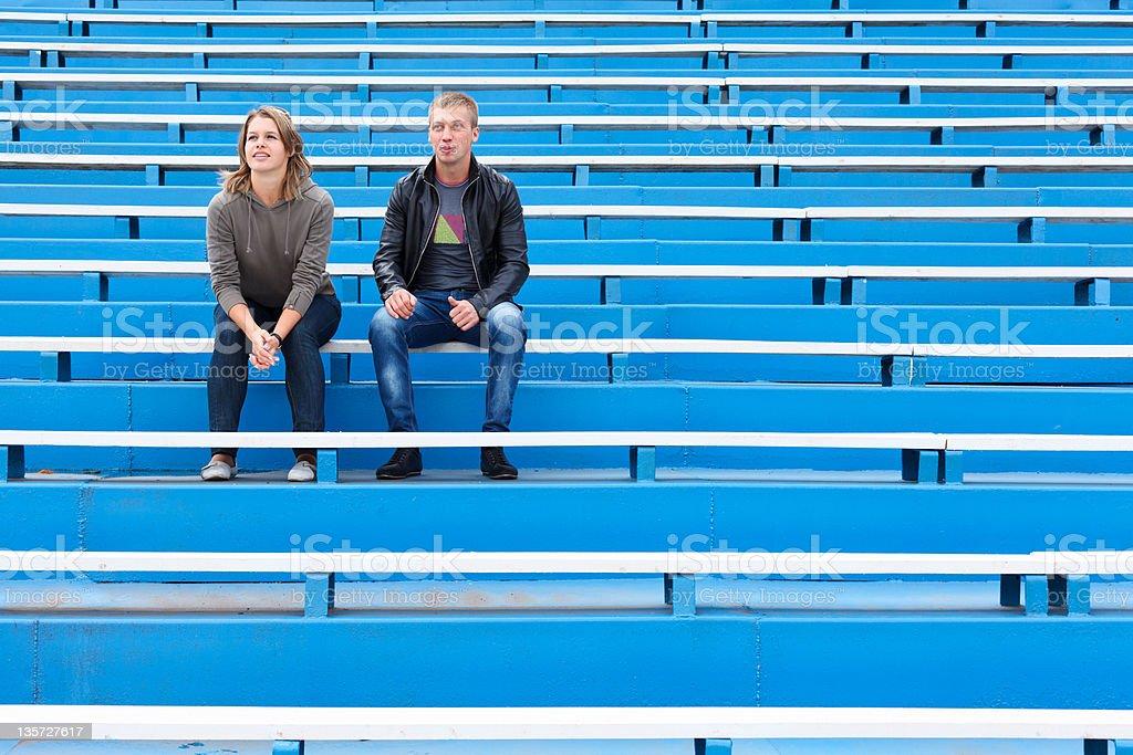 Couple on empty sports tribune stock photo