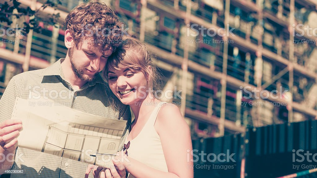 Couple on front of new house with blueprint project stock photo