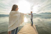 Couple on jetty, pulls out hands to reach each other