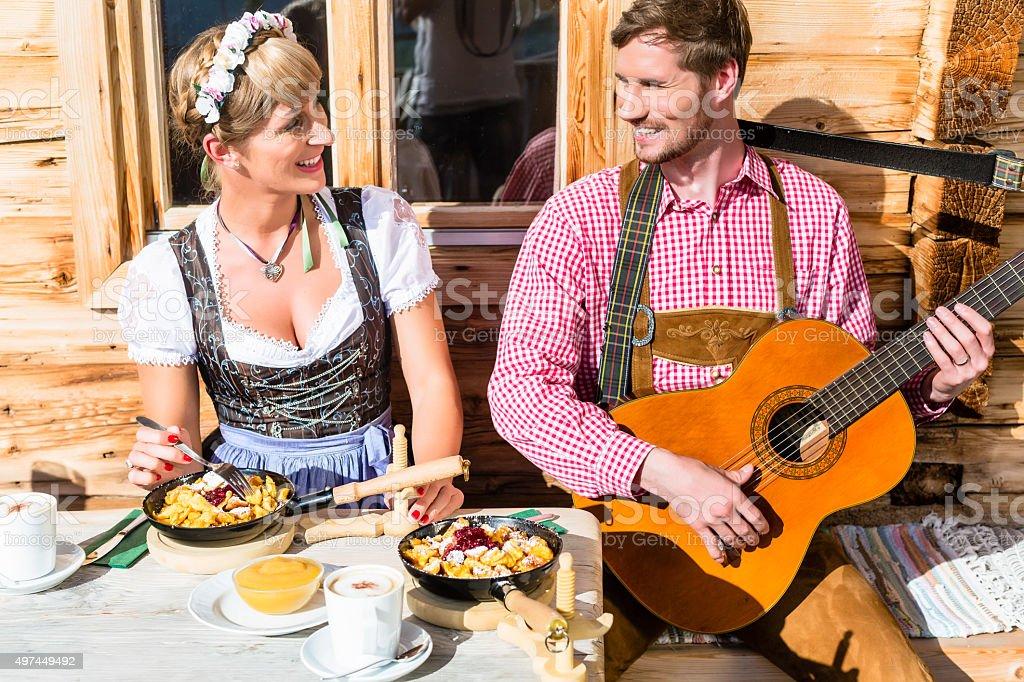 Couple on mountain hut eating Kaiserschmarrn stock photo