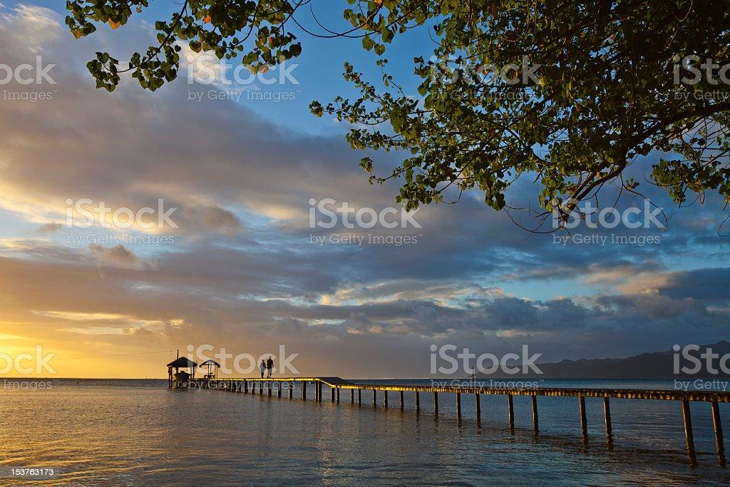 Couple on pontoon at sunset stock photo