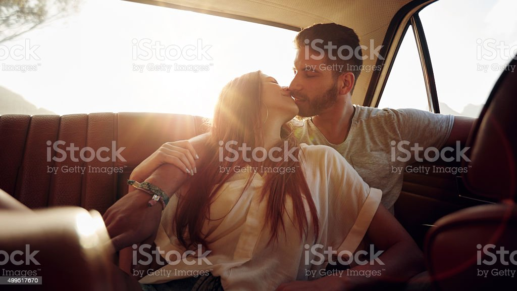 Couple on road trip sharing a romantic kiss stock photo