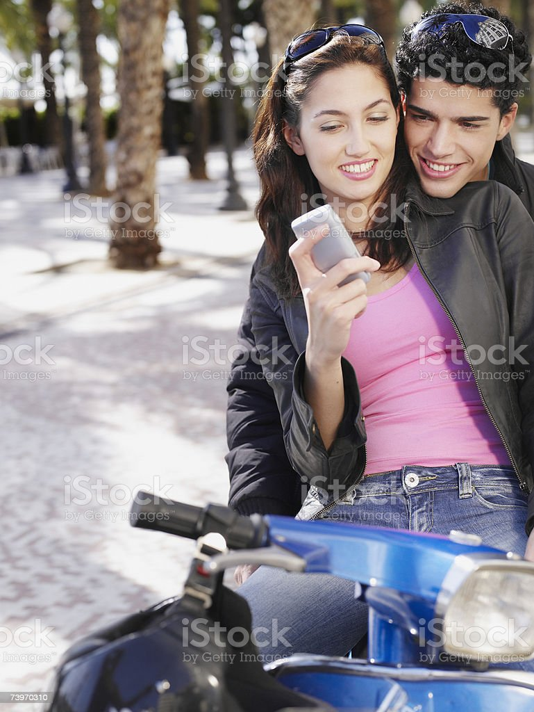 Couple on scooter looking at mobile phone royalty-free stock photo