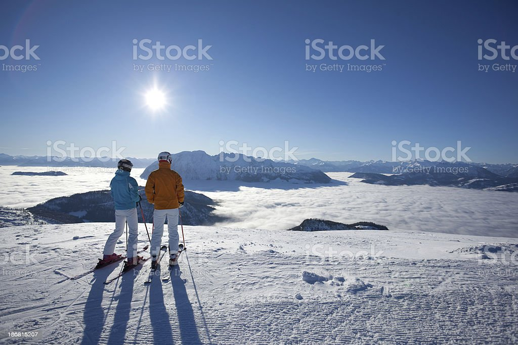 couple on skies looking at mountains appearing out of fog royalty-free stock photo