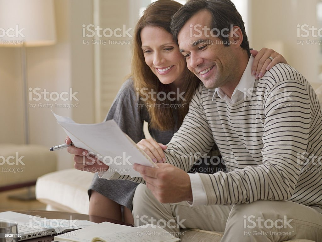 Couple on sofa reviewing paperwork royalty-free stock photo