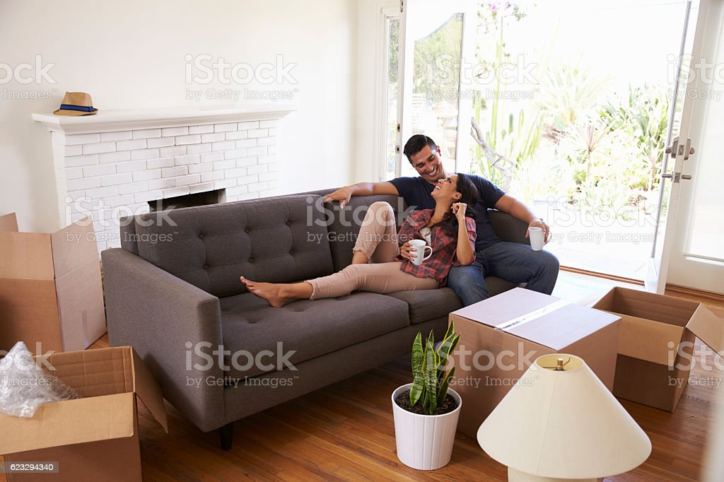 Couple On Sofa Taking A Break From Unpacking On Moving Day royalty-free stock photo