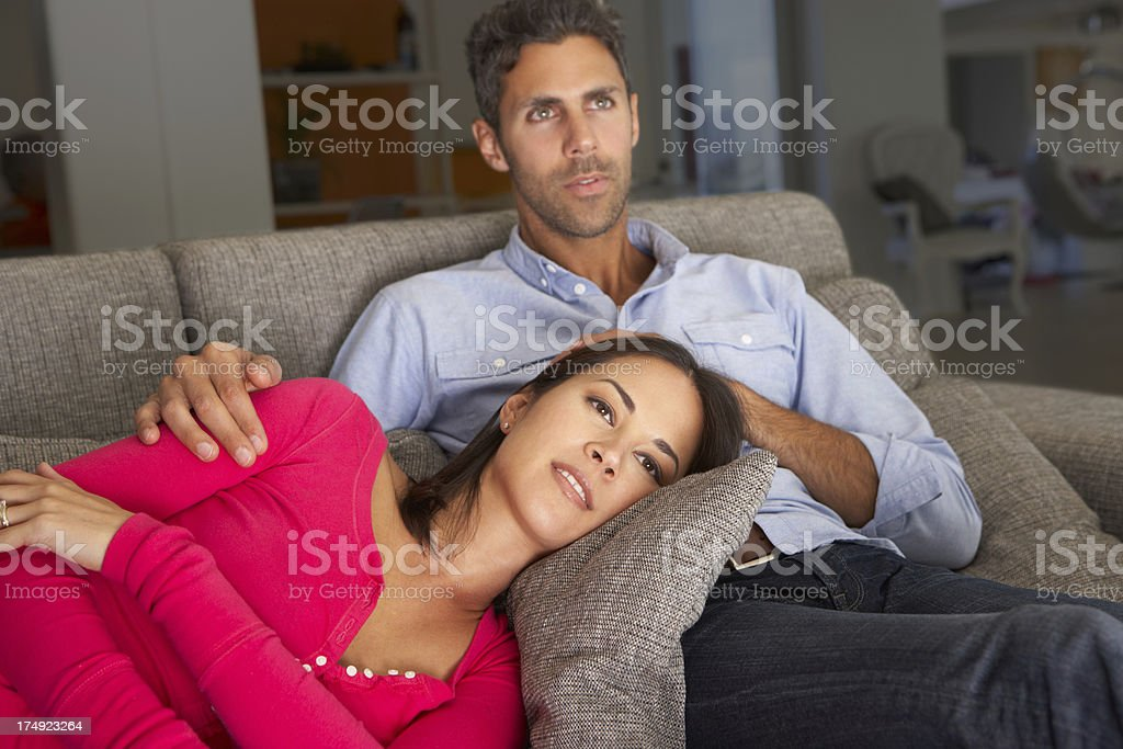 Couple On Sofa Watching TV royalty-free stock photo