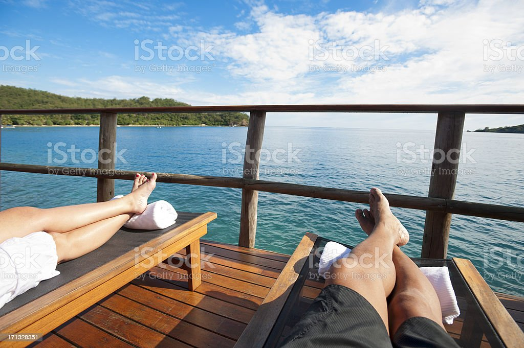 Couple on the balcony of over water bungalow, stock photo