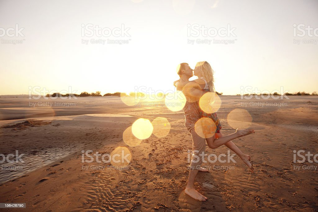 couple on the beach in evening stock photo