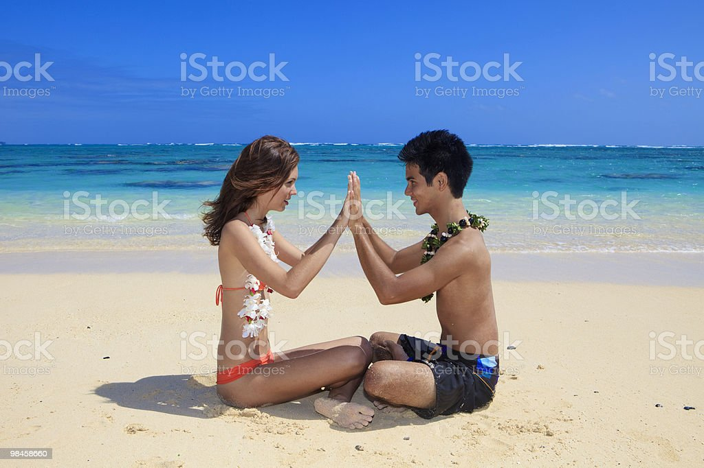 couple on the beach in hawaii touching hands stock photo
