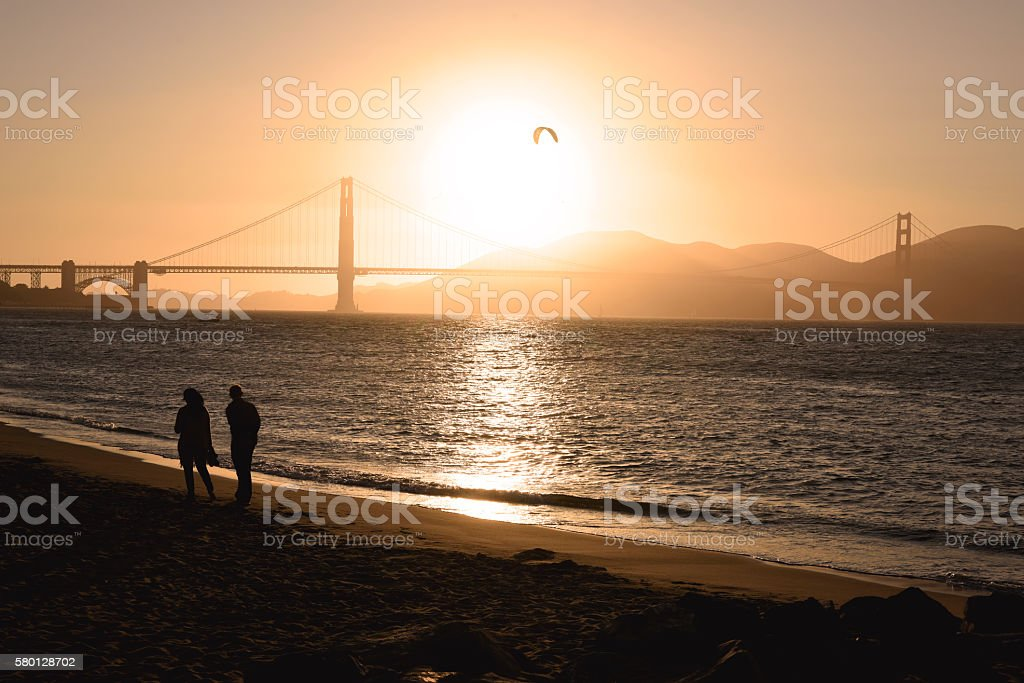 Couple on the beach in San Francisco at sunset stock photo