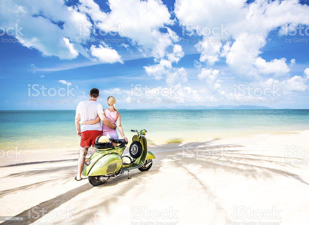 Couple on the beach with retro bike royalty-free stock photo