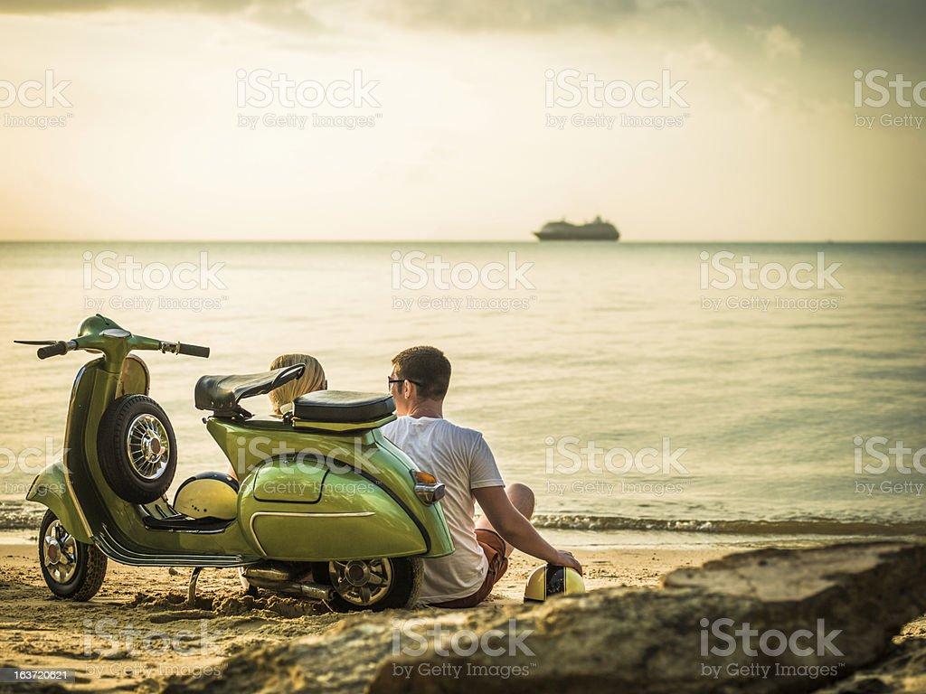 Couple on the beach with retro bike stock photo