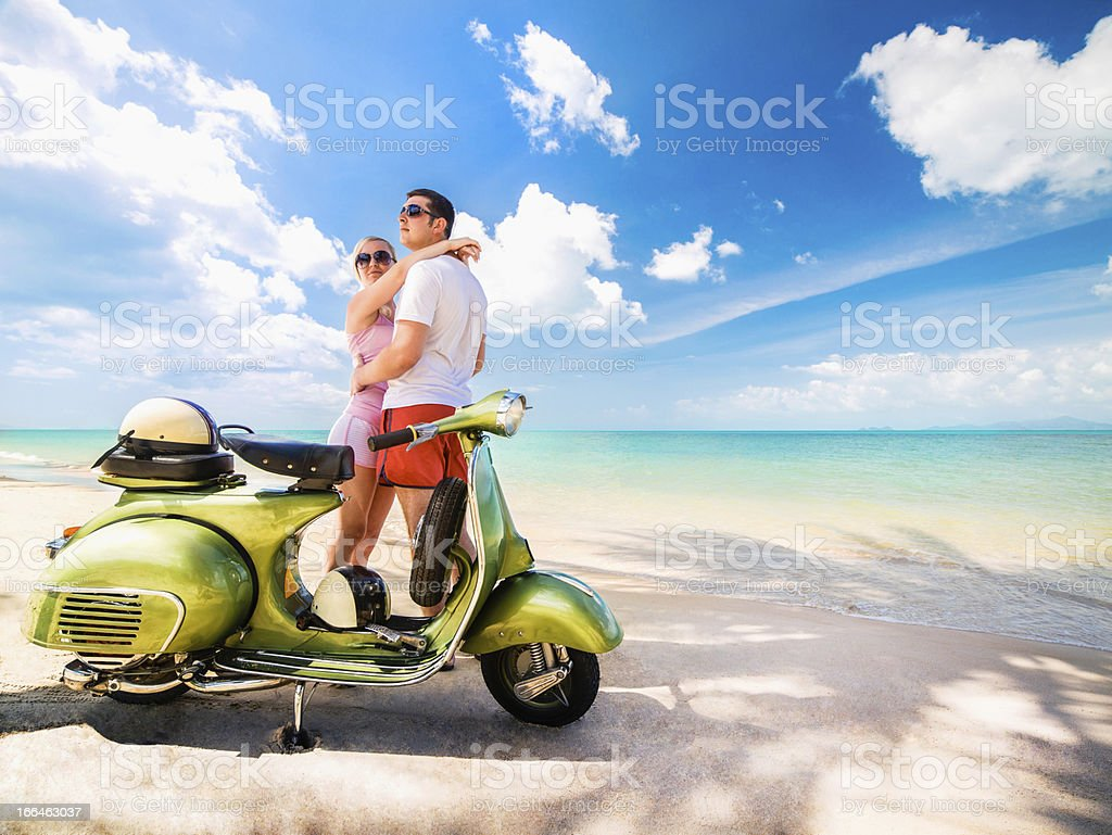 Couple on the beach with retro bike royalty-free stock photo