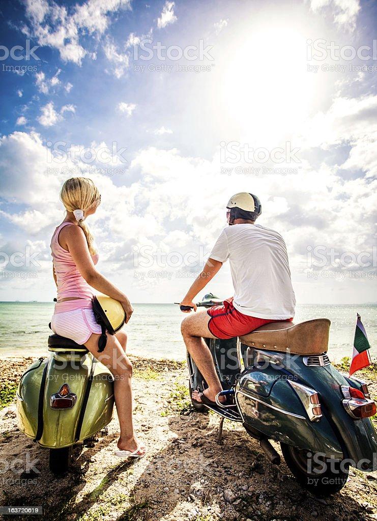 Couple on the beach with retro bikes royalty-free stock photo