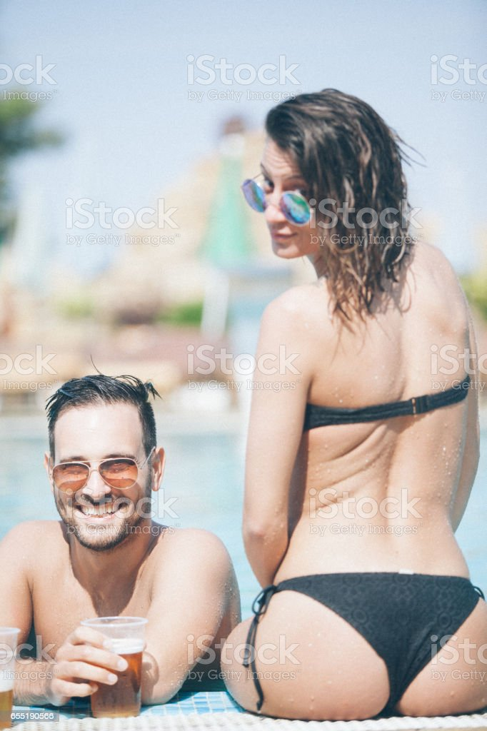 Couple on the edge of the pool stock photo
